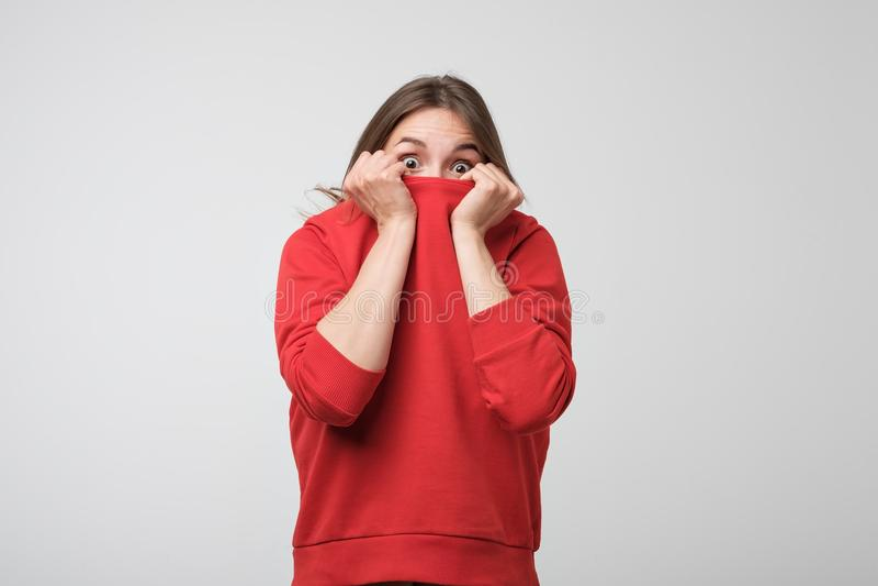 En flicka med en social fobi döljer hennes framsida i en tröja arkivfoto