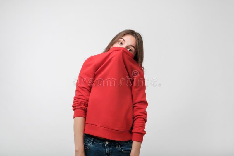 En flicka med en social fobi döljer hennes framsida i en tröja royaltyfri fotografi