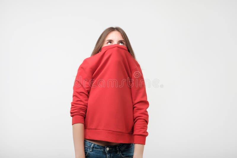 En flicka med en social fobi döljer hennes framsida i en tröja royaltyfri bild