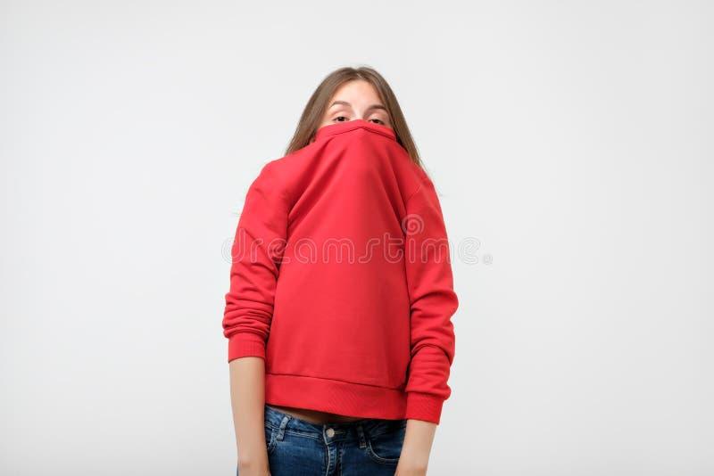 En flicka med en social fobi döljer hennes framsida i en tröja royaltyfri foto