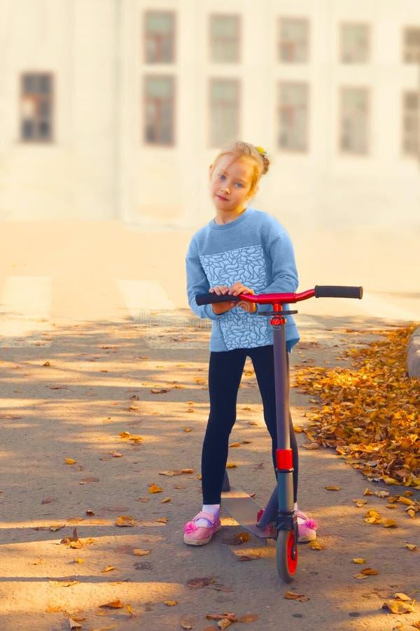 En flicka med en sparkcykel - en höstdag arkivfoto