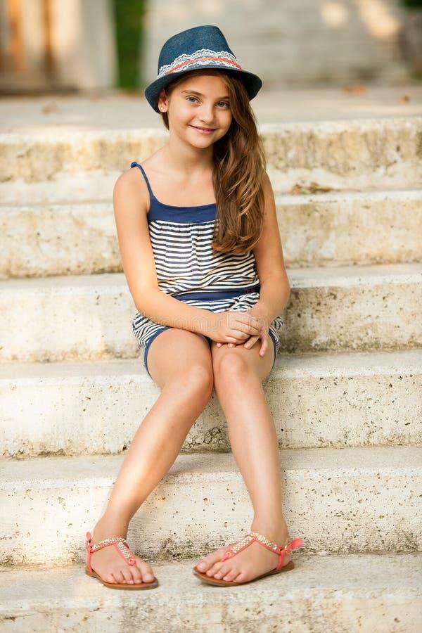 En flicka med trendigt plaggsammanträde på utomhus- trappa royaltyfria bilder