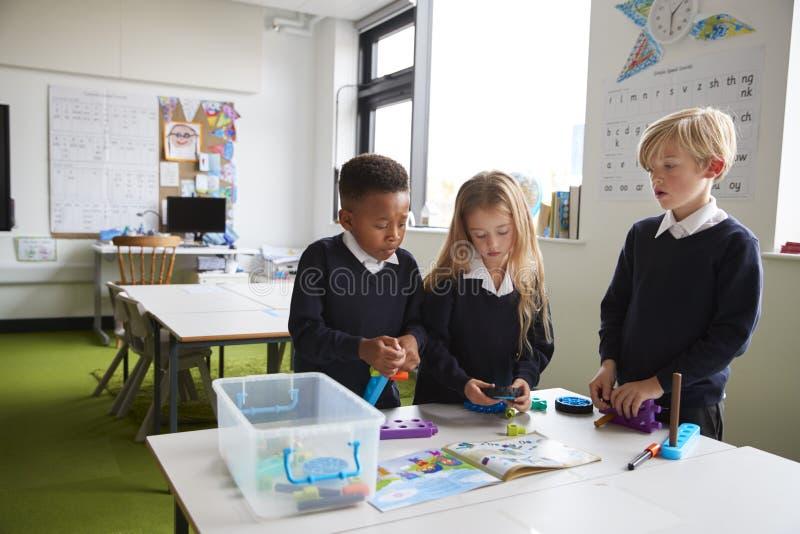 En flicka och två pojkar som står på en tabell i ett grundskola för barn mellan 5 och 11 årklassrum som arbetar samman med leksak arkivfoton
