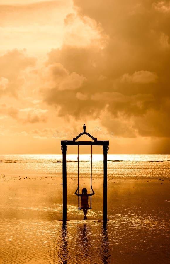 En flicka på en gunga över havet på solnedgången i bali, indonesia 3 arkivfoto