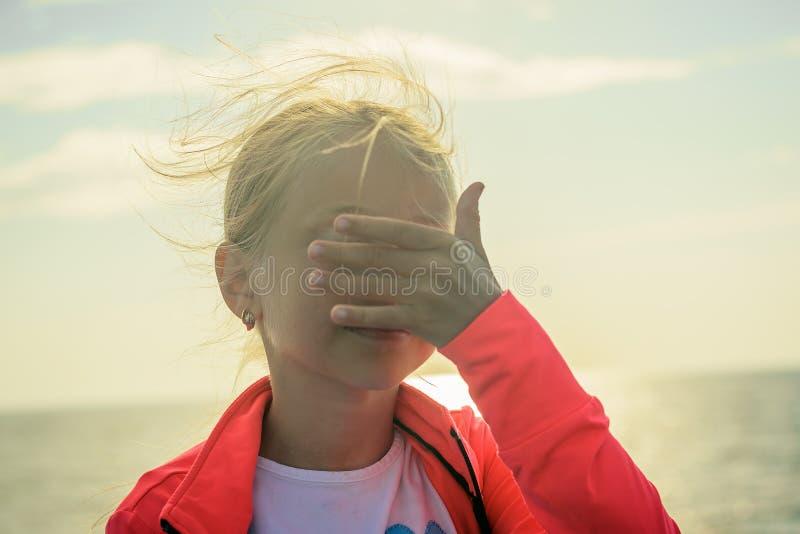 En flicka på stranden i den ljusa solen stänger henne ögon med hennes hand arkivfoto