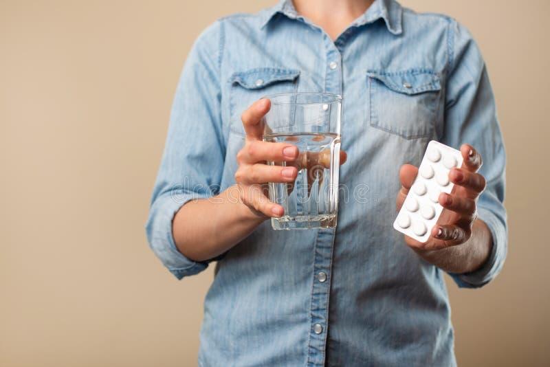 En flicka rymmer ett piller med ett exponeringsglas av vatten som g?r att dricka p? en ljus bakgrund, en sjukdom, ett apotek, f?r royaltyfri bild