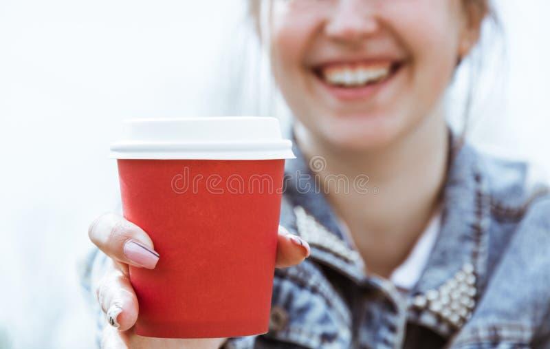 En flicka rymmer en röd pappers- kopp kaffe Exponeringsglas av kaffenärbild i hand arkivbild