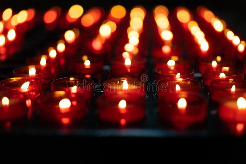 En flicka rymmer stearinljuset och ber nära altaret i kyrka arkivfoton