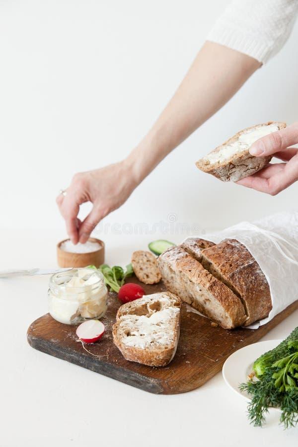 En flicka saltar en smörgås Bröd med salt, smör, gurkan och rädisor ligger på vit bakgrund arkivfoton