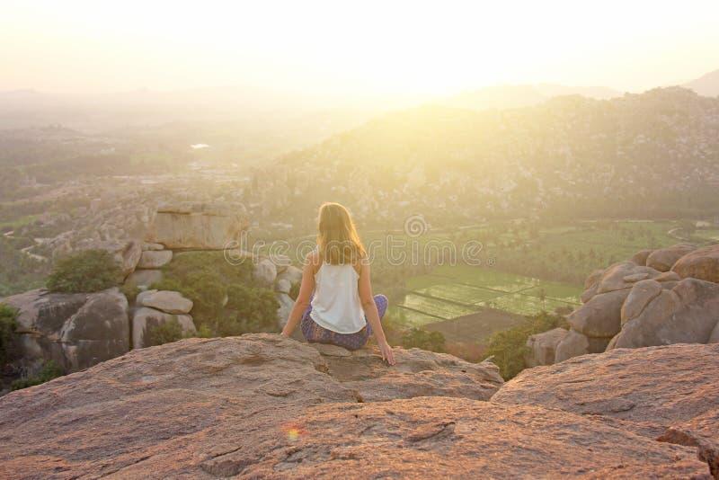 En flicka sitter med henne tillbaka på överkanten av berget och ser solnedgången på Hampi och välkomnar solen Meditation harmoni, royaltyfri foto