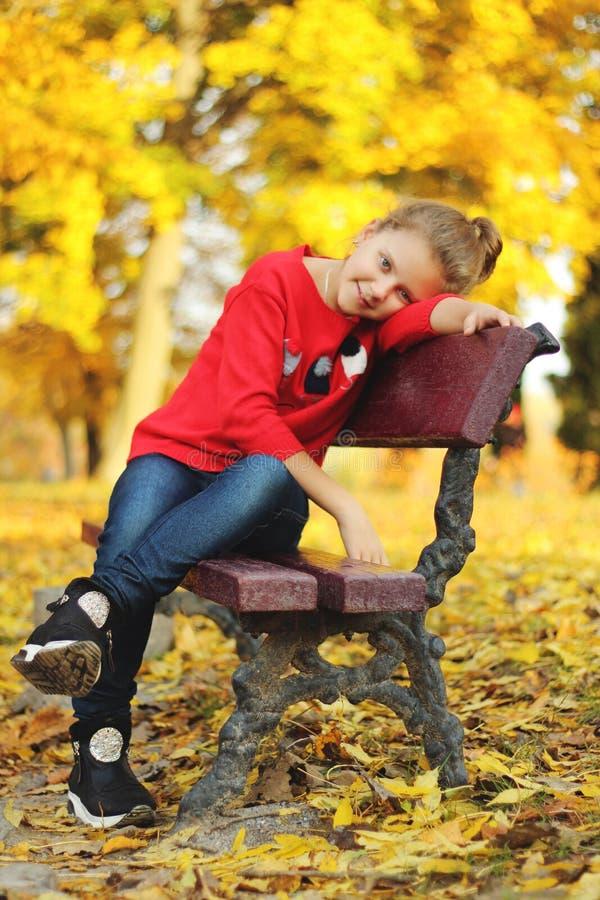 En flicka sitter på en bänk i parkera fotografering för bildbyråer