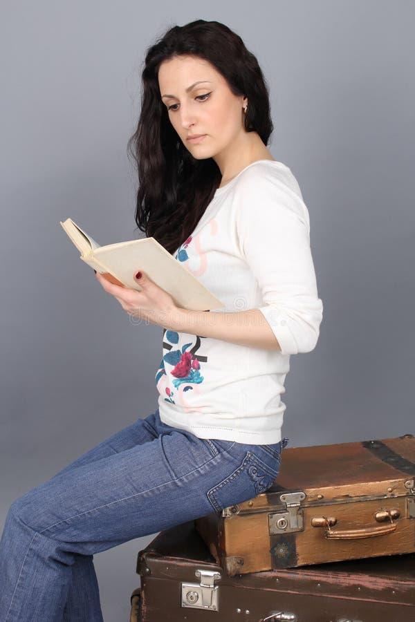 En flicka sitter på en gammal resväska och läsning en bok royaltyfri fotografi