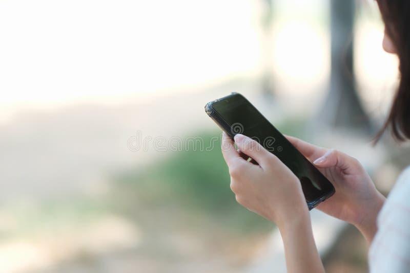 En flicka som använder den svarta smartphonen för online-shopping fotografering för bildbyråer