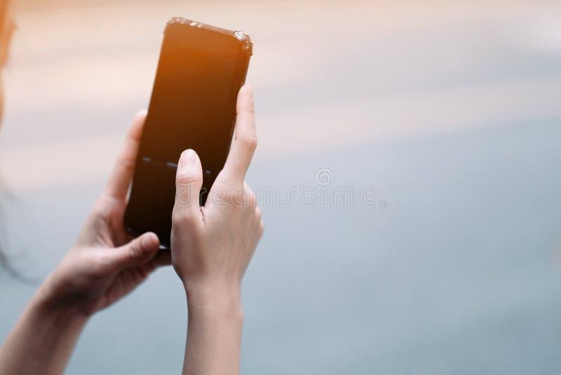 En flicka som använder den svarta smartphonen på gatan royaltyfri foto