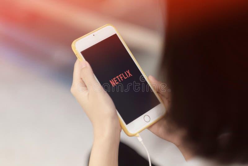 En flicka som håller ögonen på Netflix på hennes smartphone arkivfoto