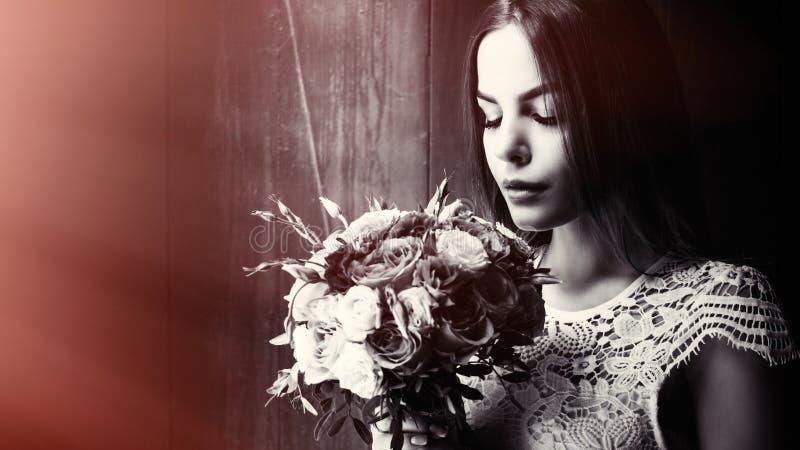 En flicka som håller blommor i händer, en ung vacker brud i vit klänning som håller bröllopsbukett, en bukett från rosenkrämen royaltyfri foto