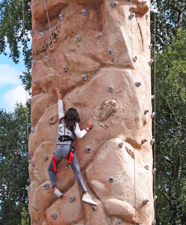 En flicka som klättrar på väggen med selet arkivbild