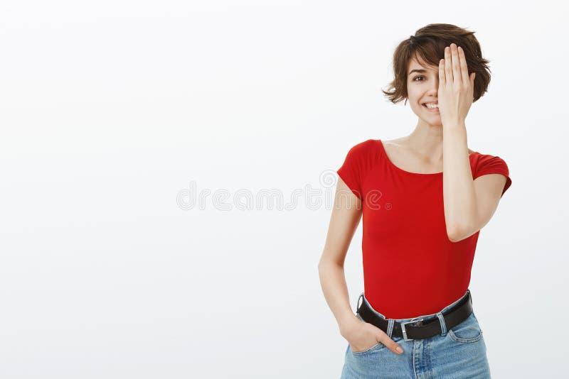 En flicka som kollar synoptiker som läser alfabet nära halva ansiktet Ett öga som ler en lätt avslappnad stående, glad lekfull arkivbilder