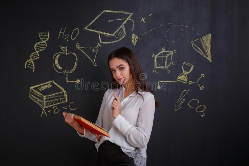 En flicka som rymmer en öppen bok som står vid ett mörkt bräde med tecken av vetenskap och kunskap arkivbild