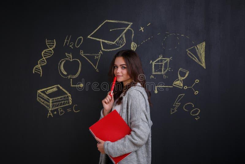 En flicka som rymmer en anteckningsbok som står nära ett mörkt bräde med bilder av tecken av idéer, vetenskap och kunskap royaltyfri fotografi