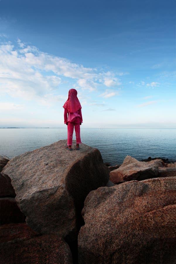 En flicka som ser in i havet royaltyfri foto