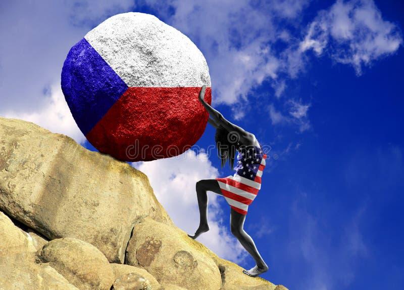 En flicka som slås in i en flagga av Amerikas förenta stater, lyfter en sten till överkanten i form av en tjeckisk flaggakontur royaltyfria bilder