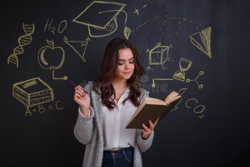 En flicka, ställningar och med ineterses som läser en bok som står bredvid brädet med en bild av vetenskap royaltyfri bild