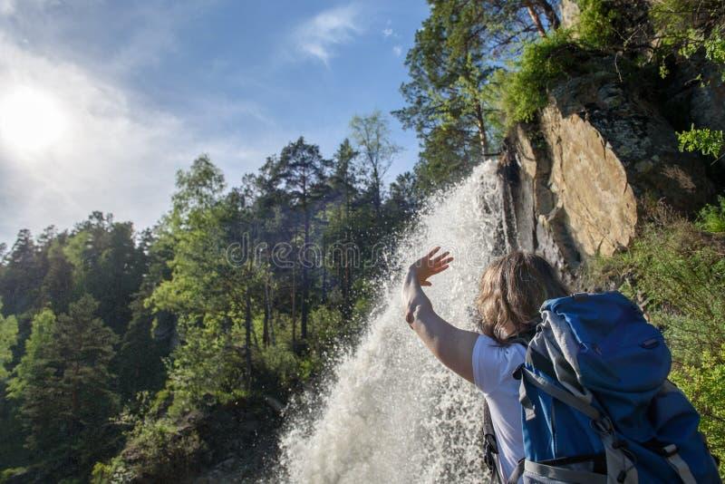 En flicka står med en ryggsäck nära en vattenfall fotografering för bildbyråer