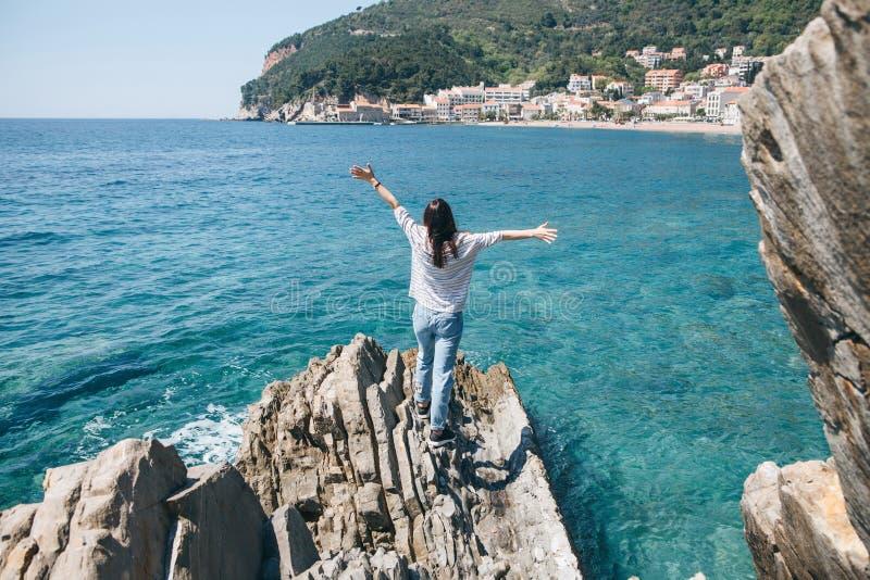 En flicka står på en stenig kust arkivbild