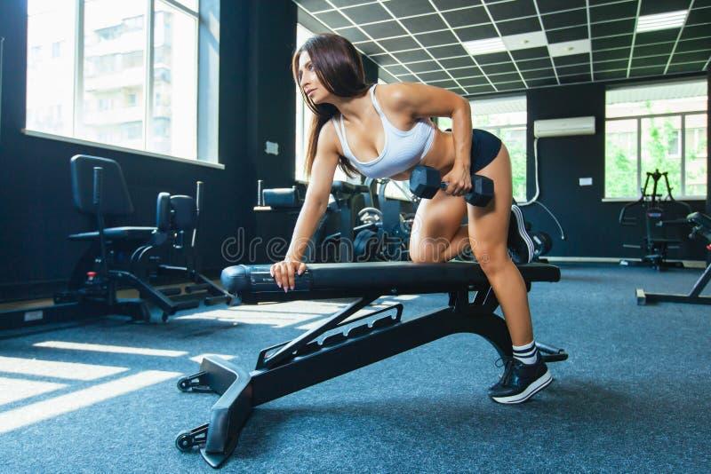En flicka utför en hantel med en hand i lutningen genom att använda en bänk övning på de mest breda tillbaka musklerna med royaltyfria bilder