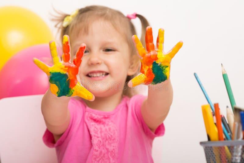 En flicka visar gömma i handflatan i målarfärg royaltyfria bilder