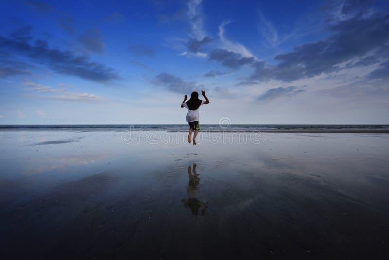En flickabanhoppning på stranden royaltyfri bild