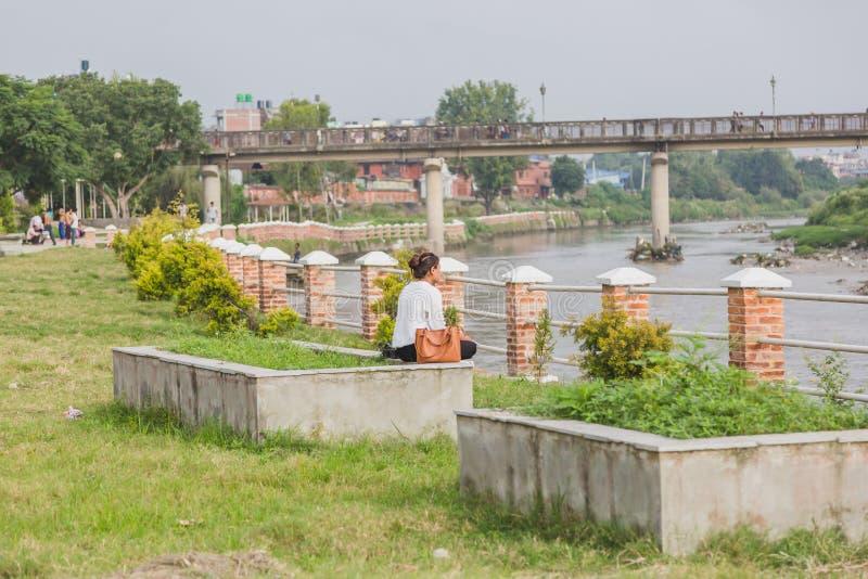 En flickaläsning på det fridsamma stället eller parkerar nära floden arkivbilder