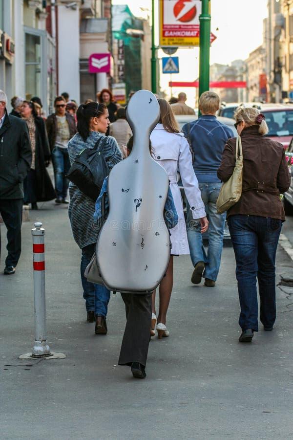 En flickamusiker bär en violoncell i ett fall på baksidan Turister som g?r runt om Moskva arkivbilder