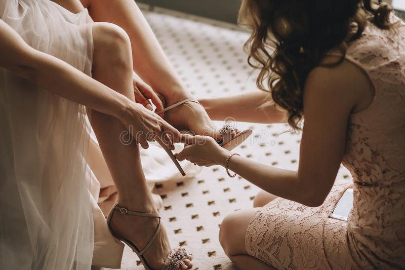 En flickvän hjälper en brud till pålagt hennes bröllopskor Den härliga kvinnlign lägger benen på ryggen closeupen royaltyfri bild