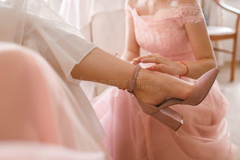 En flickvän hjälper en brud till pålagt hennes bröllopskor Härlig kvinnlig fot closeup royaltyfri bild