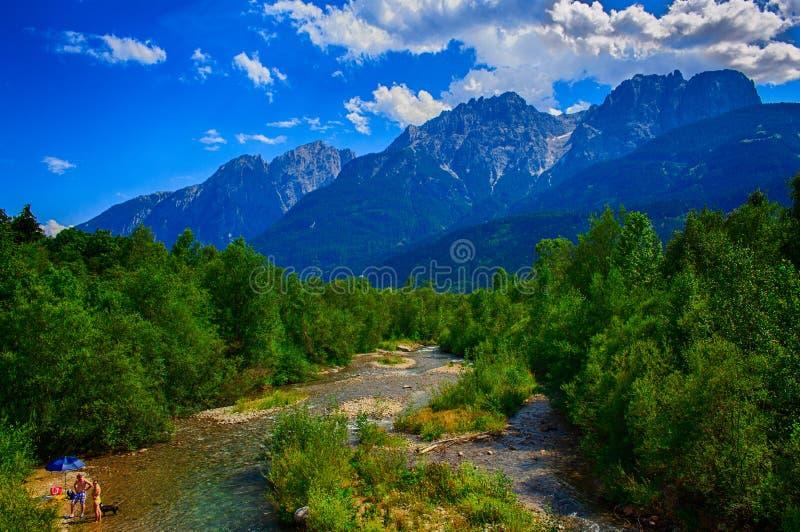 En flod kör till och med dolomitesna royaltyfria foton