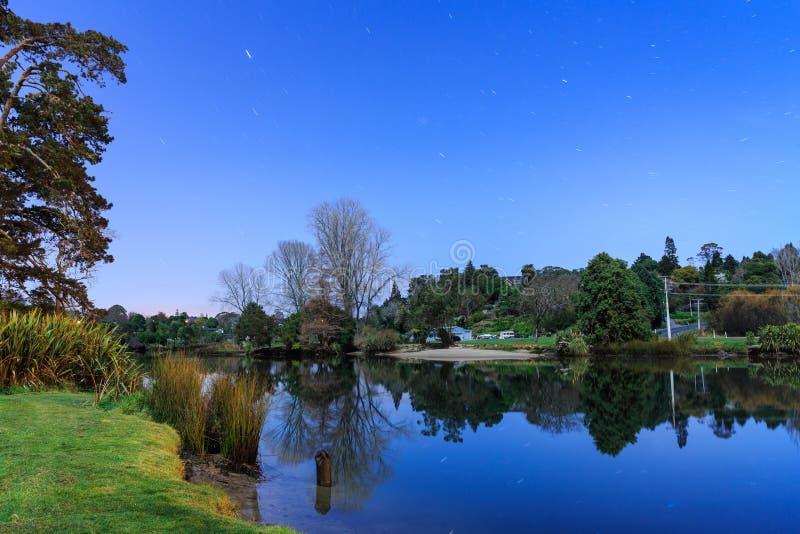 En flod på natten, med en stjärnklar himmel över royaltyfria foton