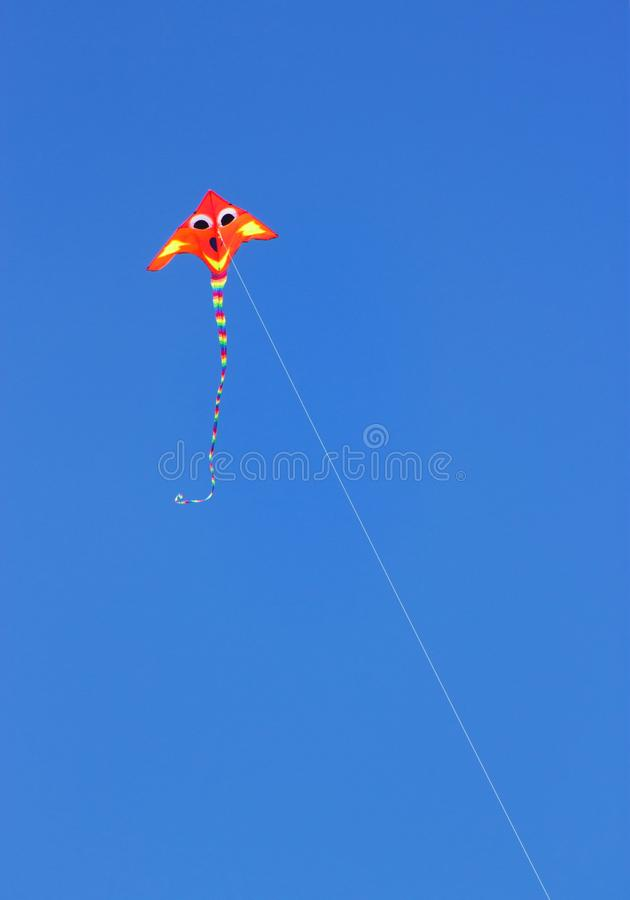 En Fluro färgade draken mot en ljus blå sommarhimmel fotografering för bildbyråer