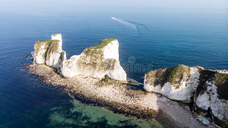 En flyg- sikt av den gamla Harry Rocks med kristallklart vatten, vita klippor och hastighetsfartyget i bakgrunden under en disig  royaltyfria foton