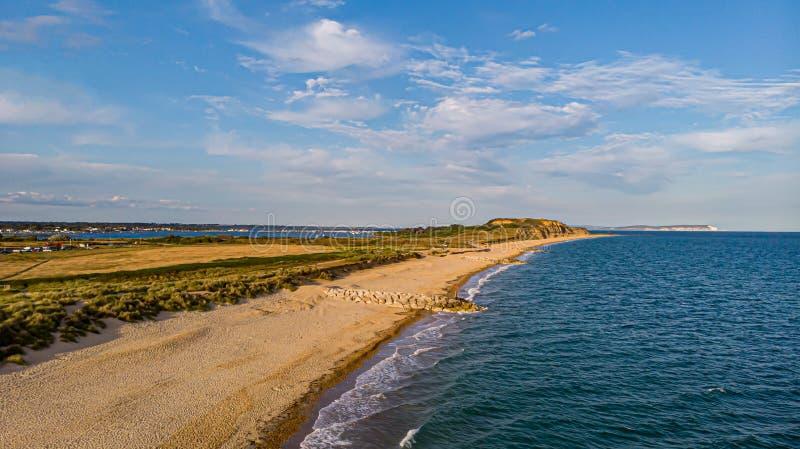 En flyg- sikt av en härlig sandig strand längs havet för blått vatten och amaizing klippor i bakgrunden på den guld- timmen under arkivfoton