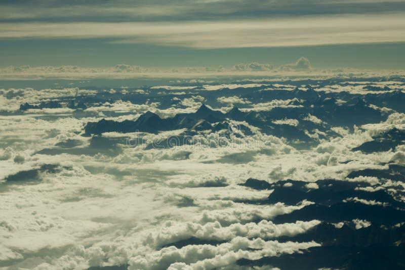En flyg- sikt av himalayan svarta konturer deserterar berg med snöig maxima under vita moln och blå himmel arkivbild