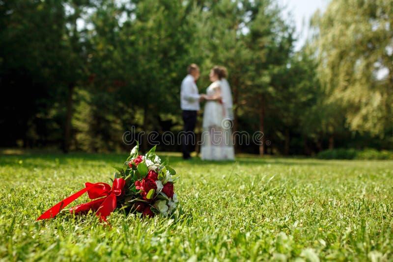 En foco, el ramo de la boda miente en la hierba contra la perspectiva de las figuras que se besan de los recienes casados Concept foto de archivo