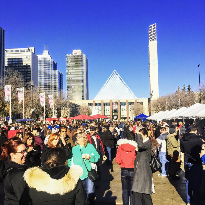 En folkmassa är upptagen på den Churchill fyrkanten framme av stadshuset i i stadens centrum Edmonton, Alberta, Kanada arkivbild