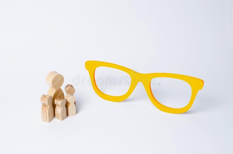En folkmassa av folk ser skulpturen av enorma gula exponeringsglas Begrepp av utbildning och vishet av äldre utvecklingar, modern arkivfoton
