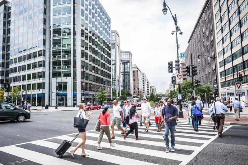 En folkmassa av folk som korsar en stadsgata på övergångsstället arkivfoto