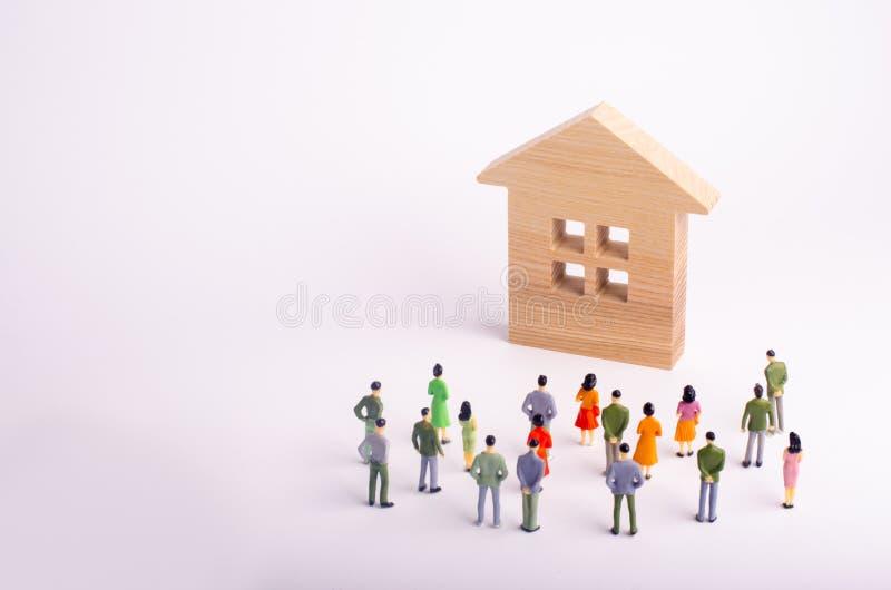 En folkmassa av folk som står och ser ett trähus på en vit bakgrund Köpa och sälja av fastigheten, hyra Affordabl arkivbild