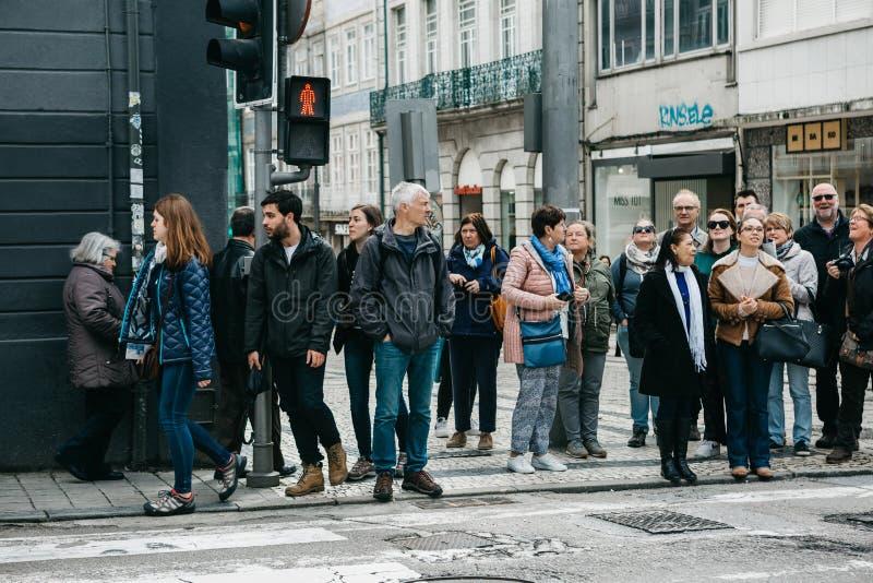 En folkmassa av folk står på en röd trafikljus royaltyfri foto