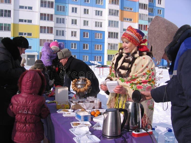 En folkmassa av folkmän, barn och kvinnor tar mat från gatuförsäljare på ferie i Novosibirsk i vintern fotografering för bildbyråer