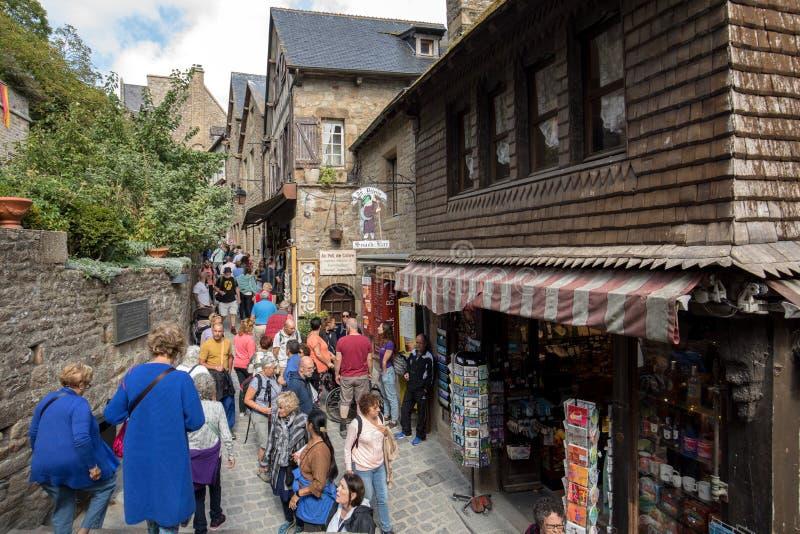 En folkmassa av turister p? storslagen Rue, den huvudsakliga gatan i Mont Saint Michele france normandy royaltyfri bild